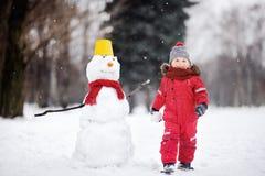 红色冬天衣裳的小男孩获得与雪人的乐趣在冬天公园 免版税库存照片