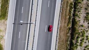 红色减速火箭的汽车驱动的鸟瞰图在日间路或高速公路的 没有在机动车路的很多汽车 股票视频