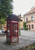 红色减速火箭的电话箱子在老镇 免版税库存图片