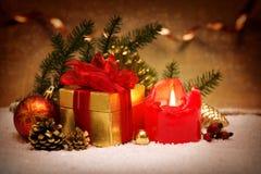 红色出现蜡烛和圣诞节礼物 免版税图库摄影