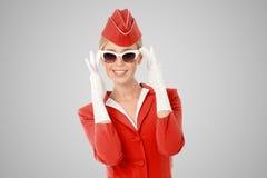 红色制服和葡萄酒太阳镜的迷人的空中小姐 库存图片