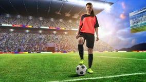 红色制服的女性足球运动员在足球场 免版税库存照片