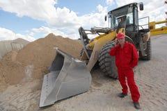 红色制服的工作者在buldozer的电话在建造场所 免版税库存照片