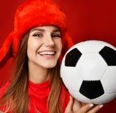 红色制服的拿着足球庆祝愉快微笑的俄国样式爱好者体育妇女球员和耳朵挡水板帽子 免版税图库摄影