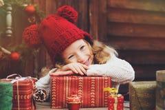 红色包裹圣诞节礼物的帽子和围巾的愉快的儿童女孩在舒适乡间别墅,装饰新年和圣诞节 免版税库存图片