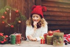 红色包裹圣诞节礼物的帽子和围巾的愉快的儿童女孩在舒适乡间别墅,装饰新年和圣诞节 图库摄影