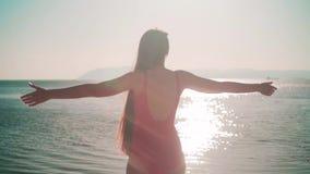 红色单件泳装的一个女孩在海滨站立 女孩站立举她的手,显示自由的迹象 影视素材