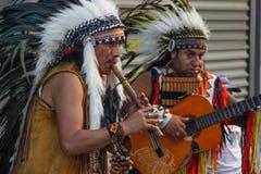 红色印度人美国本地人弹长笛和吉他在羽毛头饰 库存照片