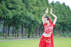 红色印度礼服的亚裔中国秀丽肚皮舞表演者 免版税库存照片