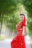 红色印度stytle礼服的亚裔中国秀丽肚皮舞表演者 库存照片