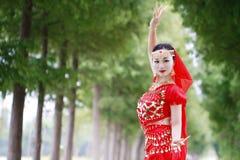 红色印度stytle礼服的亚裔中国秀丽肚皮舞表演者 免版税图库摄影