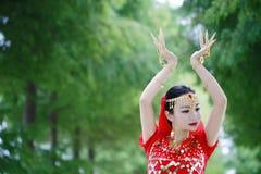 红色印度stytle礼服的亚裔中国秀丽肚皮舞表演者 免版税库存照片