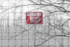 红色危险标志被张贴对有刺的篱芭在分支缠结了,警告 图库摄影