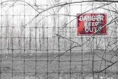 红色危险标志被张贴对有刺的篱芭在分支缠结了,警告 免版税库存照片