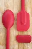 红色厨房匙子和小铲在木背景 免版税库存照片