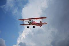 红色双翼飞机剧烈的天空 图库摄影