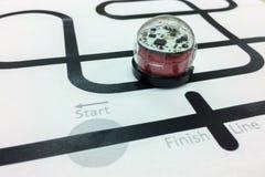 红色发光的塑料象编程的金属机器人汽车跑在黑线 免版税图库摄影