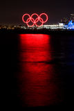 红色发光的奥林匹克圆环在港口反射了 库存照片