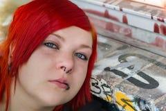 红色听见的妇女有graffity背景 库存图片