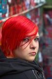红色听见的妇女有graffity背景 免版税库存照片