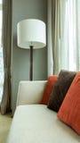 红色和布朗装饰枕头在一个偶然织品沙发有大白色灯的在客厅 免版税库存照片
