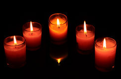 红色和桃红色蜡烛在玻璃杯子透明最密集的黑暗中 库存照片