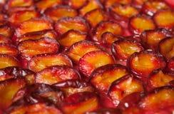 红色和桔子烘烤了李子切成了两半说谎一个平面上 免版税库存图片