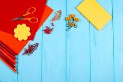 红色和橙色铅笔、毡尖的笔、便条、纸夹、文具钉子、毛毡和剪刀在蓝色木背景 免版税库存图片