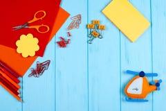红色和橙色铅笔、毡尖的笔、便条、纸夹、文具钉子、毛毡和剪刀在蓝色木背景 库存图片