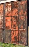 红色和生锈的金属毂仓大门,画象射击 免版税库存图片