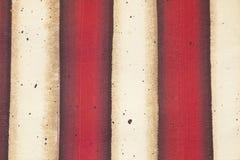 红色和白旗镶边了被绘的帆布背景与难看的东西作用的 免版税库存照片