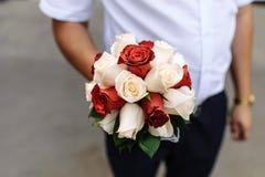红色和白玫瑰新娘花束在新郎的手上 免版税图库摄影