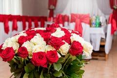 红色和白玫瑰花束在欢乐桌附近的在res 图库摄影