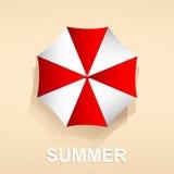 红色和白色伞顶视图在海滩沙子的 库存图片