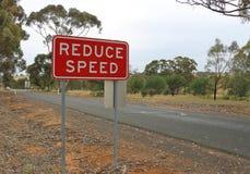 红色和白色减少速度在乡下公路的安全标志 库存图片