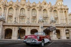 红色和白色别克敞篷车在哈瓦那歌剧前面停放了 免版税库存图片