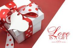 红色和白色圆点题材礼物盒当前与心脏形状礼物标记,充满爱, 免版税库存图片