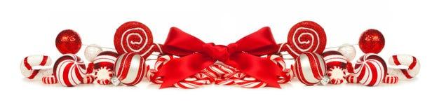 红色和白色圣诞节中看不中用的物品、弓和棒棒糖边界 库存图片