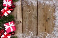 红色和白色圣诞节礼物在木头的边边界 库存图片