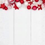 红色和白色圣诞节装饰品在白色木头的上面边界 免版税图库摄影