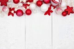 红色和白色圣诞节装饰品在白色木头的上面边界 免版税库存图片