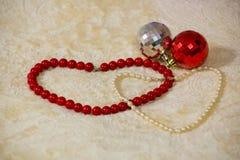 红色和白色小珠被计划以两心脏的形式在米黄毯子的圣诞节玩具旁边 免版税库存图片