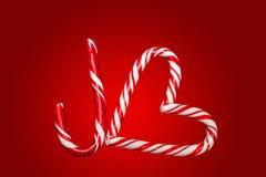 红色和白色棒棒糖在J和心脏,标志o安排了 免版税库存照片