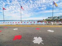 红色和白色横幅和槭树叶子装饰wal的海边 免版税库存照片