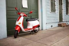红色和白色滑行车停放了一个绿色门外 库存照片