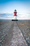 红色和白色灯塔在道路结束时 库存图片