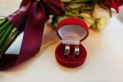 红色和白色玫瑰和丝带婚礼花束与婚礼ri 免版税库存照片