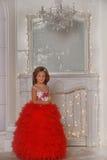 红色和白色礼服身分的年轻公主我 免版税库存照片