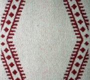 红色和白色被编织的羊毛毯子 免版税库存图片
