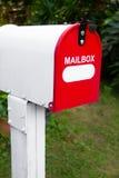 红色和白色邮箱白色绿色庭院背景 免版税库存照片